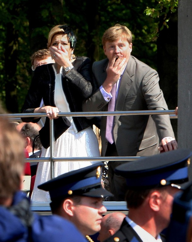 "Photo 2 Apeldoorn 30 of April 2009: Maxima clamps her one hand on the railing of the bus and the other over her mouth and nostrils, as she watches the totally unexpected terrible scene in front of her; Willem Alexander is captured with his mouth visible through his fingers in an inelegant way, one of the rare moments were his trained  official mask has fallen of; their eyes survey the disastrous scenery but also seem to be turned inward, thoughts racing through their minds; ""was this aimed at us?""; seeing the victims on the street and people rushing up to help them; seeing the crashed car; curious is that the face of the one policeman that can be seen in full profile looks the other way, as if he has not seen what has just happened and it is a face without any sign of having witnessed a disaster; it could be that as the policemen stand lower their view is blocked; nobody is seen in a pose of shrinking back from an approaching danger, or pulling themselves together after such a fear. The overall impression is that of spectators in awe."