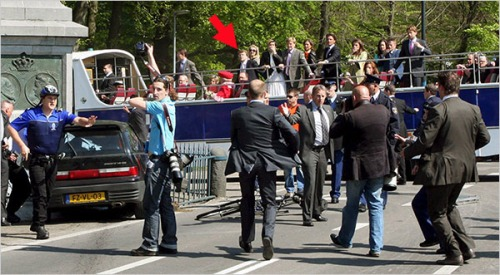 Photo 1) Apeldoorn 30 of April 2009: a photograph that did appear in the international press (possibly made by Albert Nieboer a photographer specialized in documenting royals) and that may be send it for the next World Press Photo competition and standing a good chance becuase of its complexity; with two (press) photographers being halted or interrupted in their trade right after the moment that Karsten T. crashed into the monument (with frieze pictures of the grandmother and father of Queen Beatrix visible), while in the open bus in the background the actual Dutch queen Beatrix (red costume and hat) can be seen.  This picture must have been made with a tele-lens which gives the wrong impression of the royal bus being very close to the monument and crashed car. This photograph is also taken at a short while after the car has crashed into the monument, A the moment of impact the royal bus was starting to make a curve and  arriving at the crossing. I added a red arrow that points at Prince Constantijn in the bus. The policeman at the left with the blue shirt seems to grab for his pistol and one wonders why he is doing so.  In the available pictures and videos of the Apeldoorn drama in the press and on the Internet I could not find any policeman or security officer grabbing or pointing a gun during the short moment of the deadly trajectory of the assault car.  It looks as if the policeman in the blue shirt tries to halt the photographing activity of the man with the light blue shirt and many camera's. The guys with the suits must be security officers of the royal family.