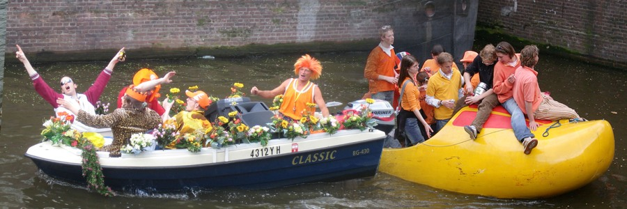 The less fortunate classes enjoying their boat party during Queens-Day in the canals of Amsterdam; notice the big sound system packed in the small boat in the left hand picture element
